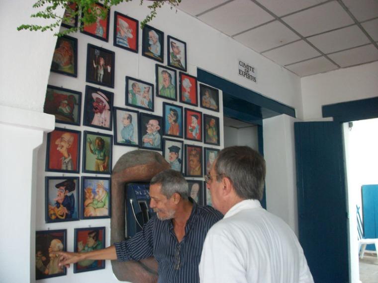 Julio Méndez, Presidente de la UNEAC en Holguín, muestra las caricaturas del Comité de Expertos al amigo Jorge Wejebe, de visita en la ciudad. 3 de noviembre de 2015. VDC FOTO/Luis Ernesto Ruiz Martínez.