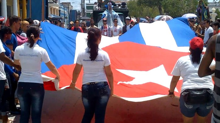 Luego de la inauguración oficial de la edición 23 de las Romerías, jóvenes holguineros trasladan la bandera y el hacha hasta la Loma de la Cruz, punto más alto de la ciudad. Foto: Luis Ernesto.