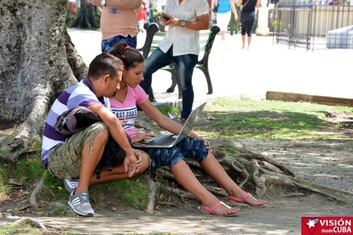 Usuarios de la WIFI de ETECSA sentados a la sombra de un árbol para navegar en internet, ante la susencia de mejores condiciones. VDC FOTO/Luis Ernesto Ruiz Martínez.