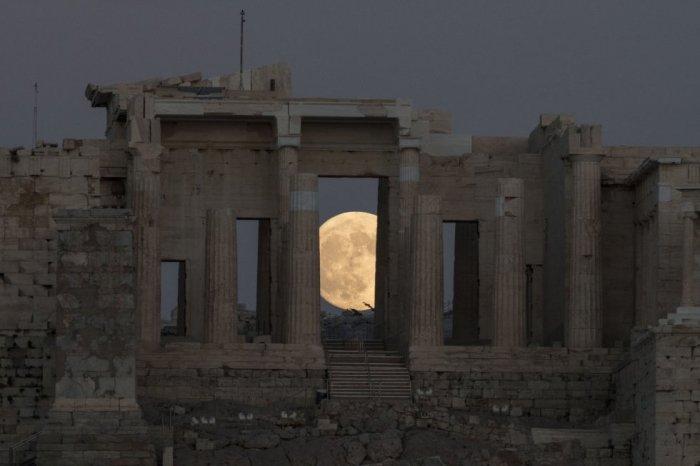 La luna tras el Acrópolis de Atenas. ANDREA BONETTI (EFE)