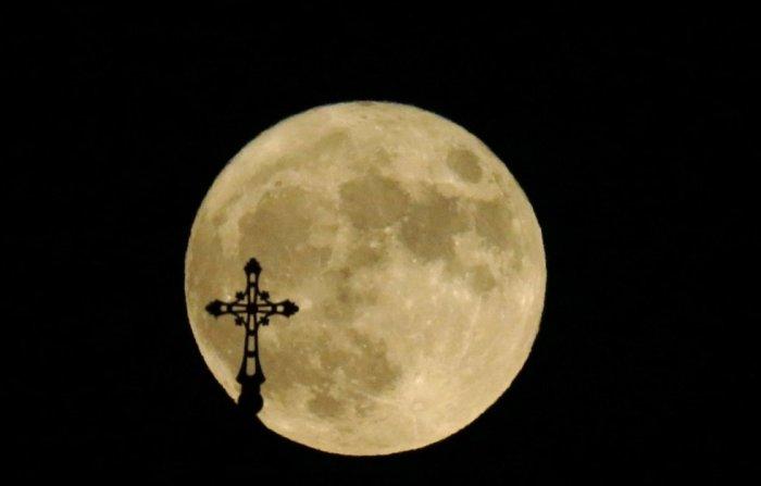 La cruz de una iglesia sobre la superluna en Tbilisi (Georgia). DAVID MDZINARISHVILI (REUTERS)