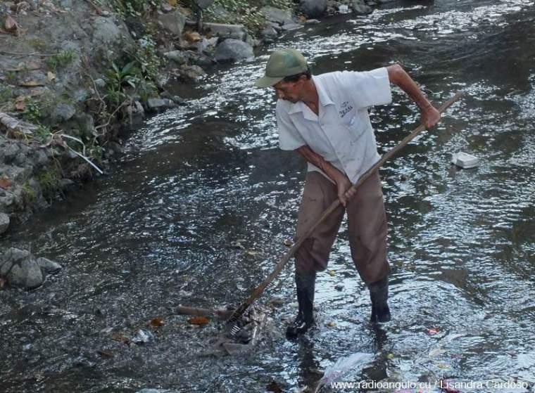 Miguel Fernández en plena labor de limpieza en el río Jigüe de la ciudad de Holguín. Foto: Lisandra Cardoso