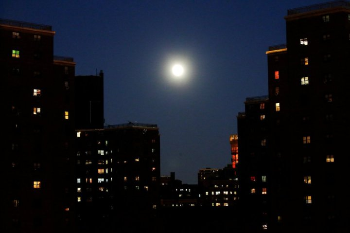 La luna se cuela entre los edificiones de Manhattan en New York. EDUARDO MUNOZ (REUTERS)