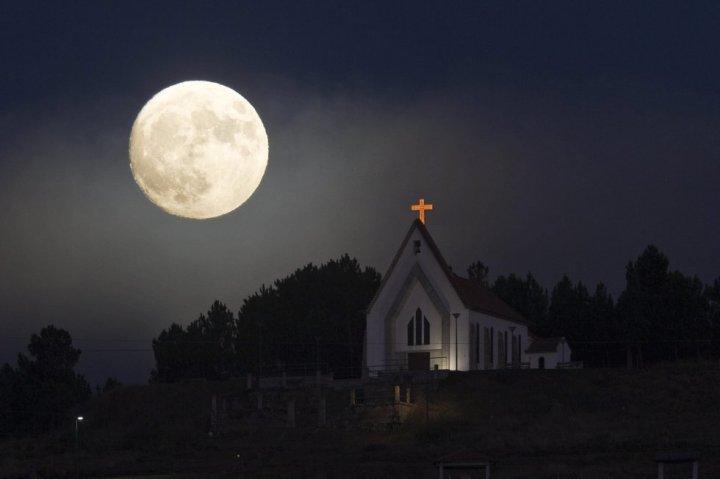 La superluna junto a la iglesia de Nuestra Señora de la Concepción en Vila Pouca de Aguiar, al norte de Portugal. PEDRO SARMENTO COSTA (EFE)