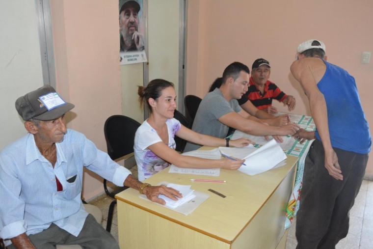 Milena y José Alberto (segunda y tercero, de izquierda a derecha), atienden a un elector del Colegio 4 de la Circunscripción 82 del municipio Holguín. VDC FOTO/Luis Ernesto Ruiz Martínez.