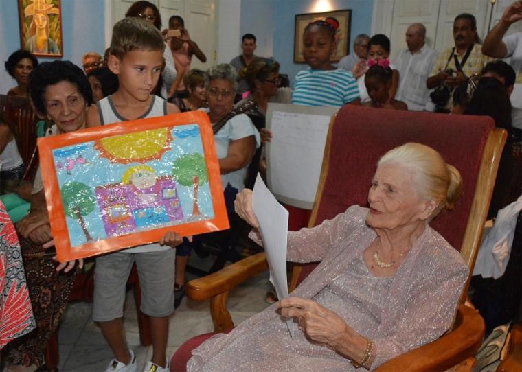 Niños integrantes del Taller Meñiques del Futuro regalan a la poetisa cubana Carilda Oliver Labra, Premio Nacional de Literatura, pinturas inspiradas en sus poemas. Foto: Yenly Lemus Domínguez/ACN.